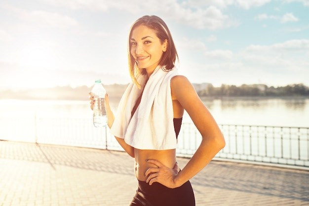 水のボトルとタオルを保持している女性