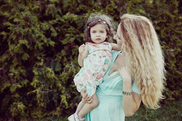 Счастливая мать и дочь смеются вместе на открытом воздухе