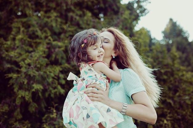 幸せな母と娘が屋外で一緒に笑って