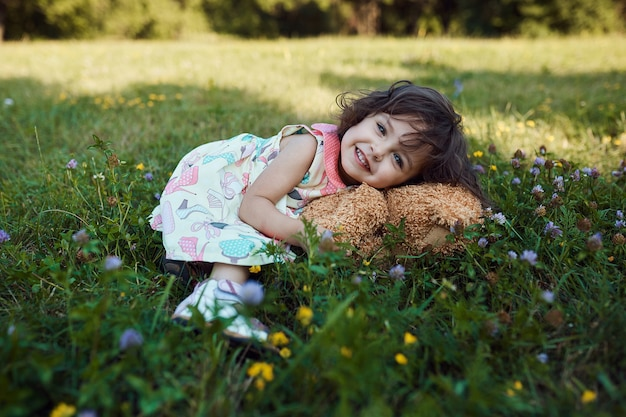 Милая улыбающаяся девочка обнимает мягкую игрушку медведя
