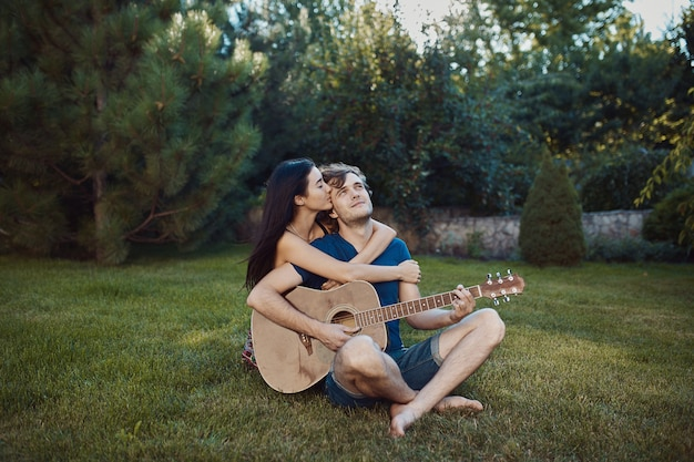 庭の芝生の上に座ってロマンチックなカップル