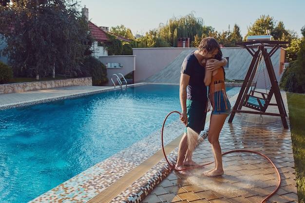 楽しんでいるカップルが庭のホースでお互いを注ぐ