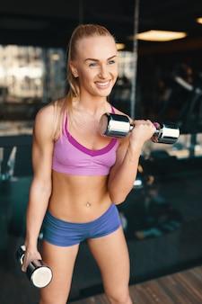 ジムで腕をトレーニングしながらダンベルで運動をしている若い白人女性