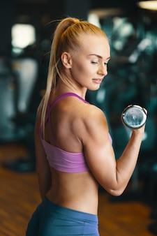 Молодая женщина в розовом топе и мини-шортах делает упражнения с гантелями
