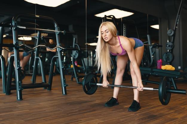 Белокурая спортсменка в мини-шортах поднимает штангу на тренировку в спортзале