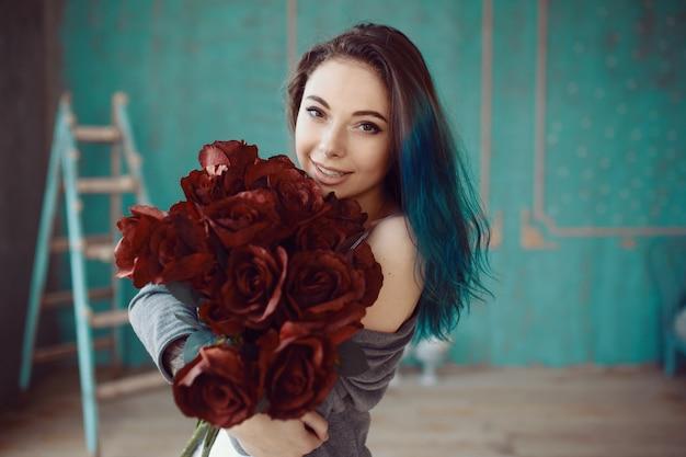 バラの花束を持つ若くて美しい女性