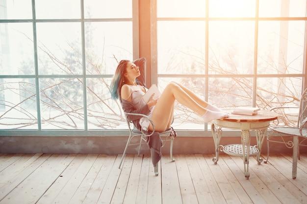 Книга чтения молодой женщины сидя около окна