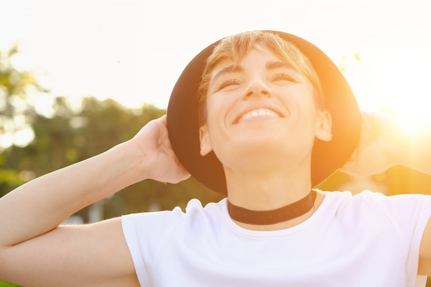 Портрет женского хипстера с естественным макияжем и короткой стрижкой, наслаждающейся отдыхом на свежем воздухе