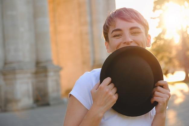 美しい女性の目を示す帽子の後ろに顔を隠す