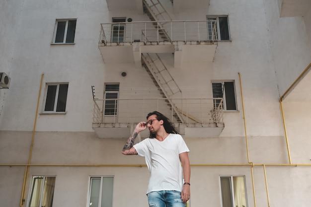 スタイリッシュな男性が建物のシーンでポーズ