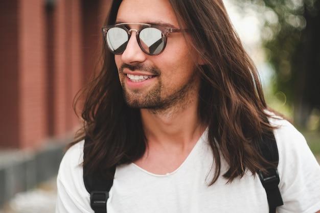 笑みを浮かべて都市のシーンにサングラスをかけた肖像画魅力的な男