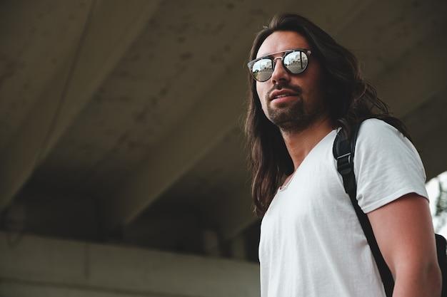 Модель носит модные солнцезащитные очки, отражающие город