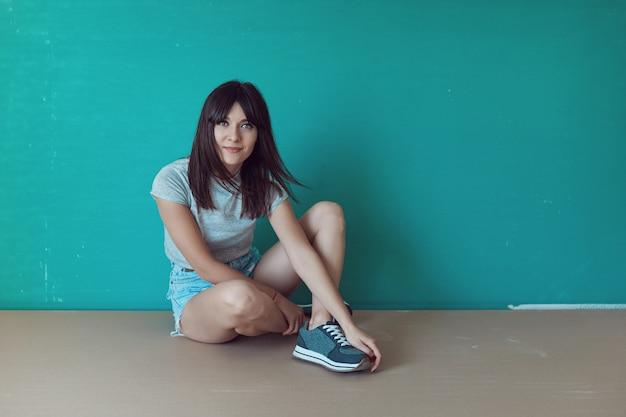 Молодая женщина с рубашкой на зеленой стене
