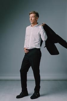 ハンサムな金髪の若い男がエレガントなスーツでポーズ