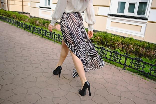 高いファッショナブルな服で女性の足のクローズアップ