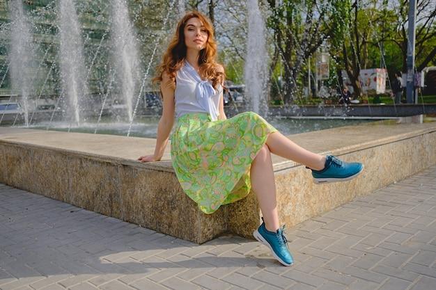 Красивая женщина сидит возле фонтана