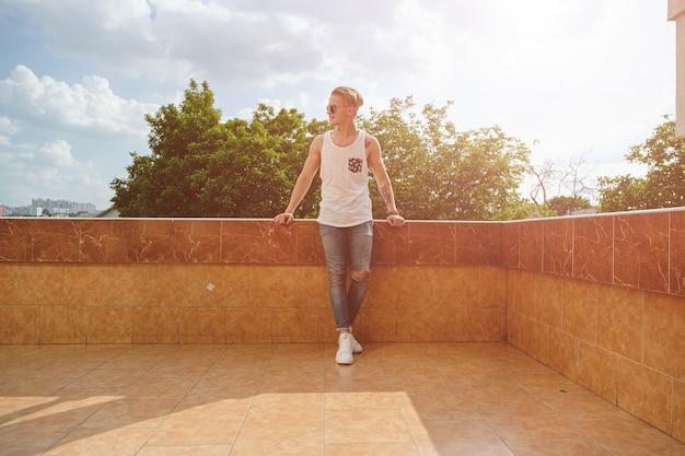若い男がリラックスして、ブイに立っている間晴れた日を楽しんでいます