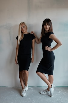 Две красивые женщины в черном платье в помещении