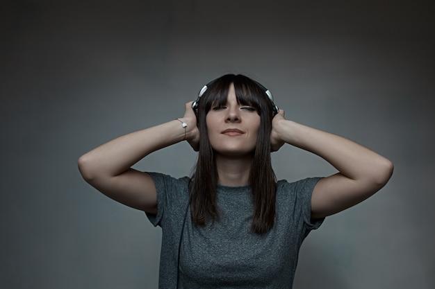目を閉じてヘッドフォンを保持している若い女性