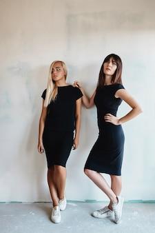 Женщины в платье позирует на стене