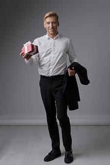 Стильный бизнесмен держит подарочную коробку