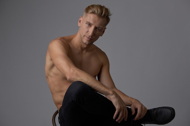 Красивый мускулистый молодой человек позирует
