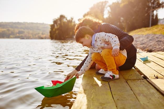 Маленький мальчик играет с игрушкой бумажный корабль на берегу озера
