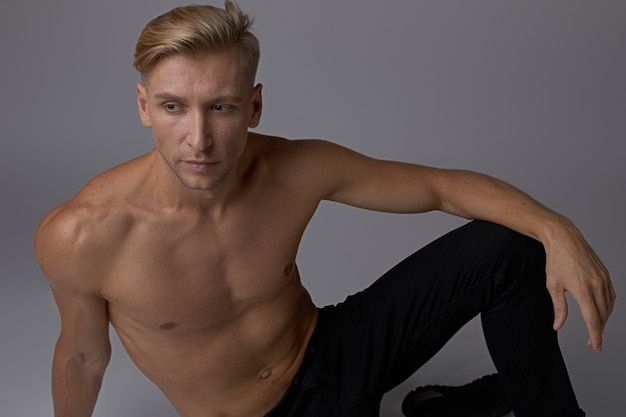 Портрет сидящий мужчина позирует голым торсом