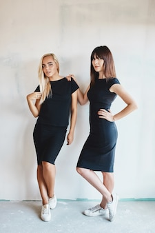 壁にポーズをとって黒のドレスの女性