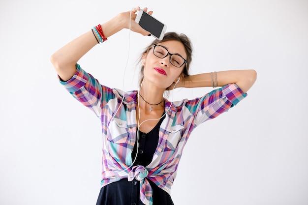 音楽を聴くヘッドフォンを持つ若い女性のクローズアップの肖像画