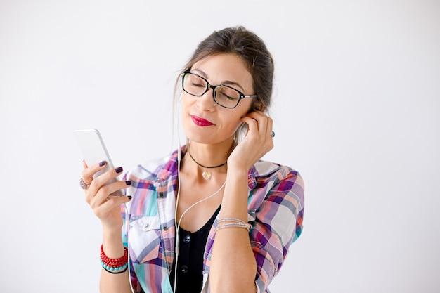 音楽を楽しむメガネの魅力的な若い女性