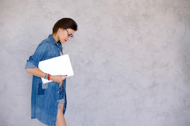 Молодая женщина профиль держит ноутбук
