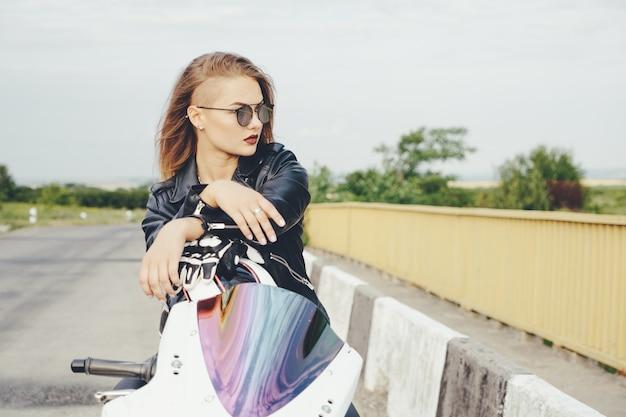 オートバイの革の服のバイク少女