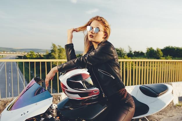 Байкер девушка в кожаной одежде на мотоцикле