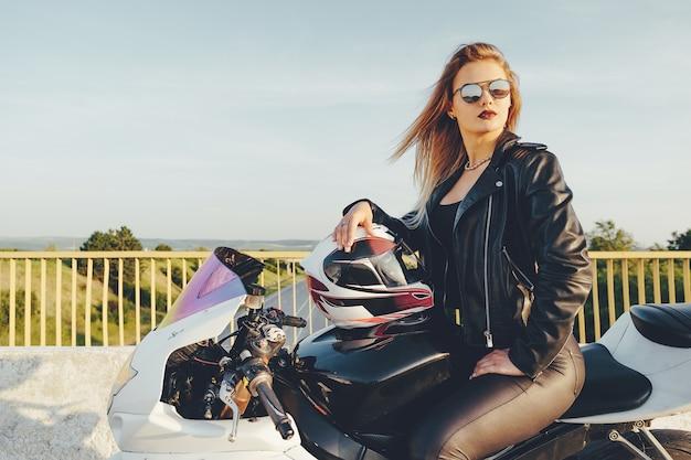 バイクを運転してサングラスを持つ美しい女性