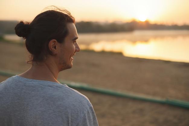 Красивый мужчина улыбается в парке