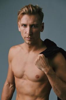Красивый мускулистый молодой человек позирует в студии
