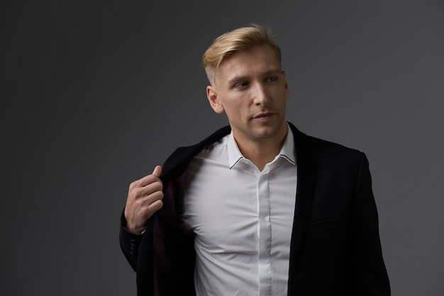 ハンサムな金髪の若い男がスタジオでポーズ