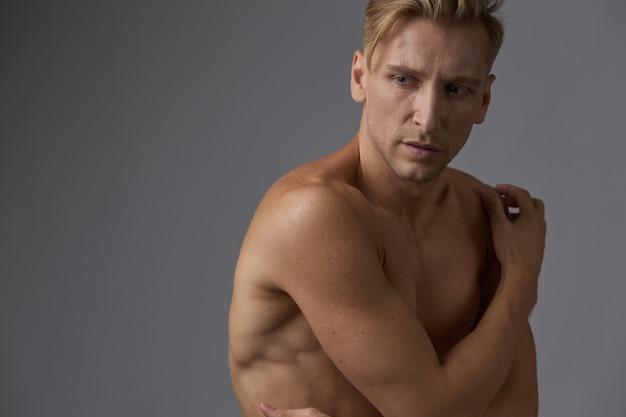 ハンサムな筋肉の若い男がスタジオでポーズ