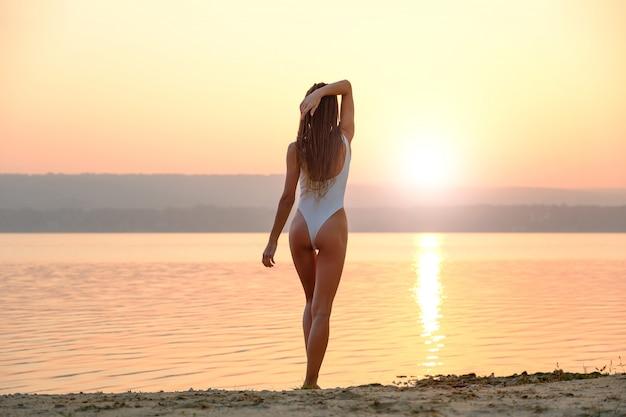 日の出のビーチに立っている文字列水着の若い女性