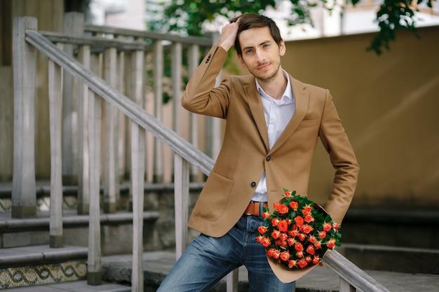 Мужчина проводит рукой по волосам, держа букет роз