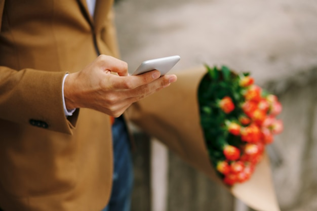 彼の手で携帯電話を保持している男
