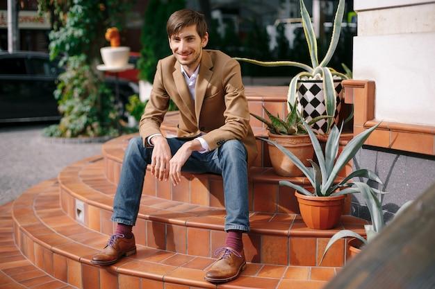 ヴィンテージの円形階段に屋外で座っている笑顔のスタイリッシュな若者