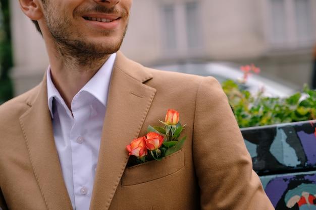 Крупным планом человек, одетый в стильный жакет с тремя розами в поке