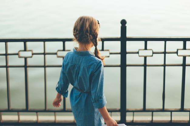 Крупным планом вид сзади ребенка, глядя на озеро