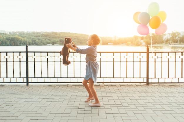 屋外でテディベアと遊ぶ女の子