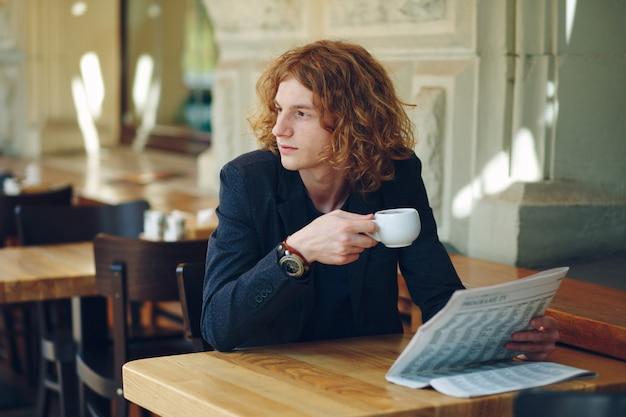 Молодой красноватый мужчина пьет кофе, глядя на право
