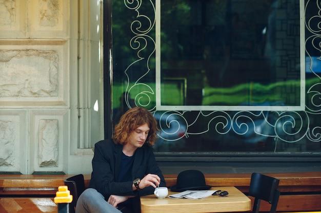 Портрет интересного красноватого мужчины, смешивающего кофе на открытом воздухе