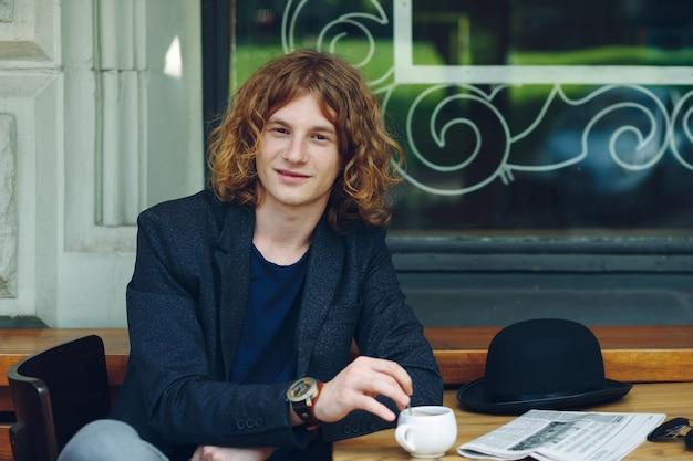 Портрет интересный красноватый мужчина позирует с кофе