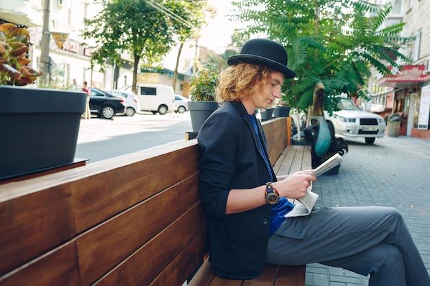 Кудрявый хипстер на деревянной скамейке в городе